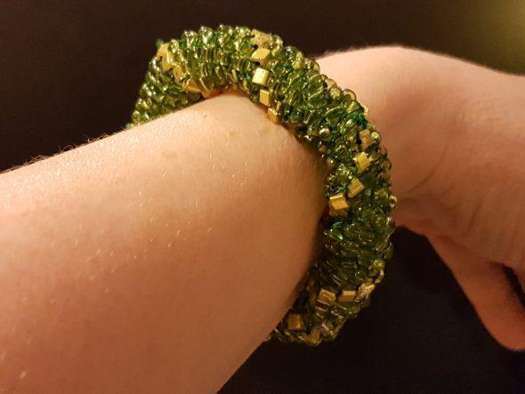 Zöld-arany karkötő karon